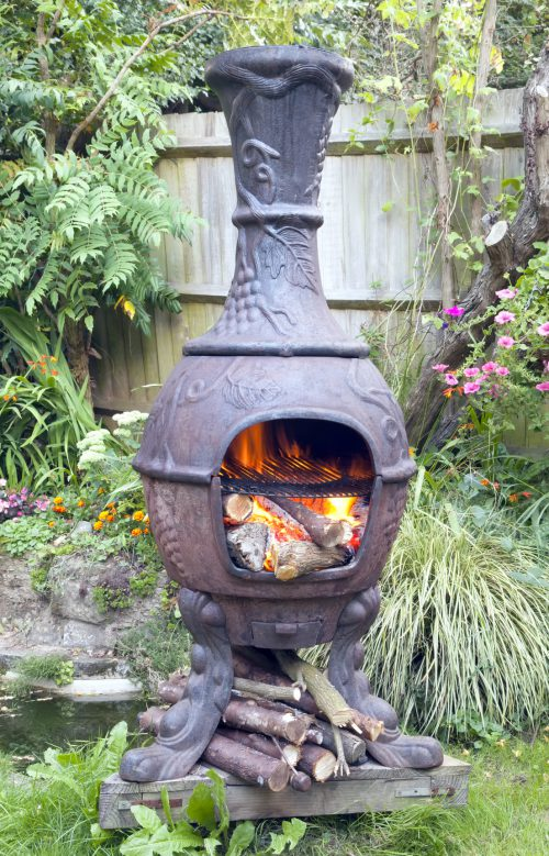 Rustic cast iron Mexican chiminea style wood burning stove with flames, in summer cottage flower garden